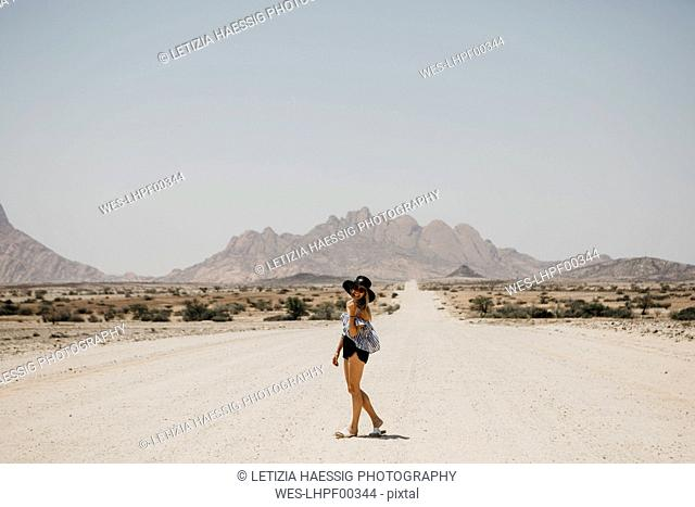 Namibia, happy woman on the road to Spitzkoppe