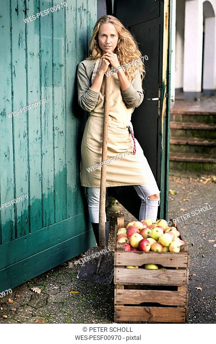 Portrait of confident woman standing at crate with apples