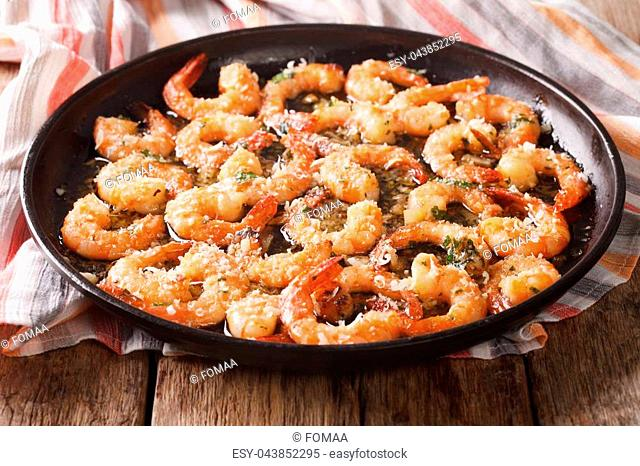 flavorful food: shrimp in garlic sauce with parmesan cheese and herbs closeup on the table. horizontal