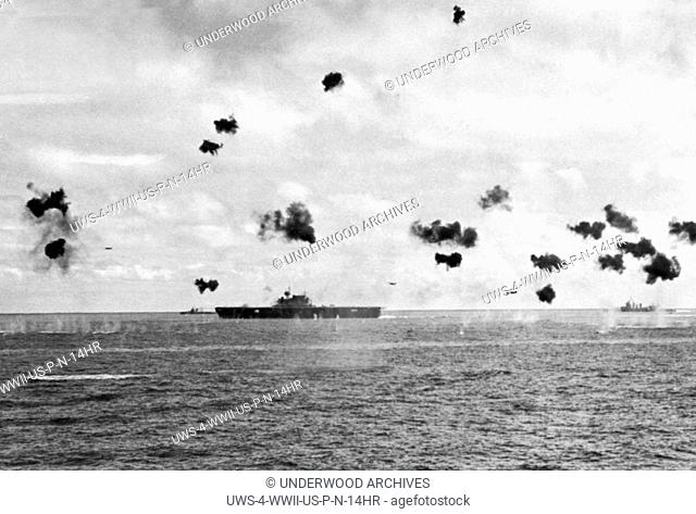 Midway Island, Pacific Ocean: June, 1942 Low flying Japanese torpedo planes come in from the right flying amidst bursting anti-aircraft shells as they aim for a...