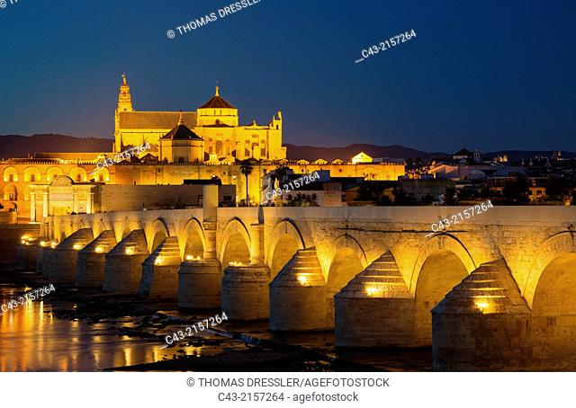 Córdoba's Puente Romano, spanning the Guadalquivir river, and the Mezquita in the background. Illuminated at dusk. Córdoba, Córdoba province, Andalusia, Spain