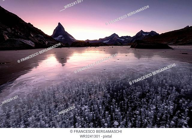Frozen Riffelsee lake by Matterhorn at sunset in Switzerland, Europe