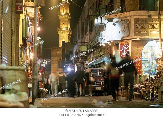 Muslim souk. Narrow streets of city. Night. Cars,people. Minaret lit up