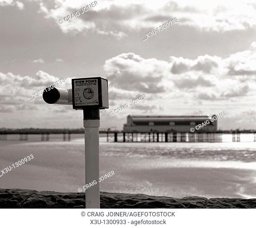 Grand Pier at Weston-super-Mare, Somerset England  In the foreground a coin operated telescope on the seafront