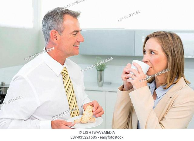 Happy business couple having breakfast in the kitchen at home