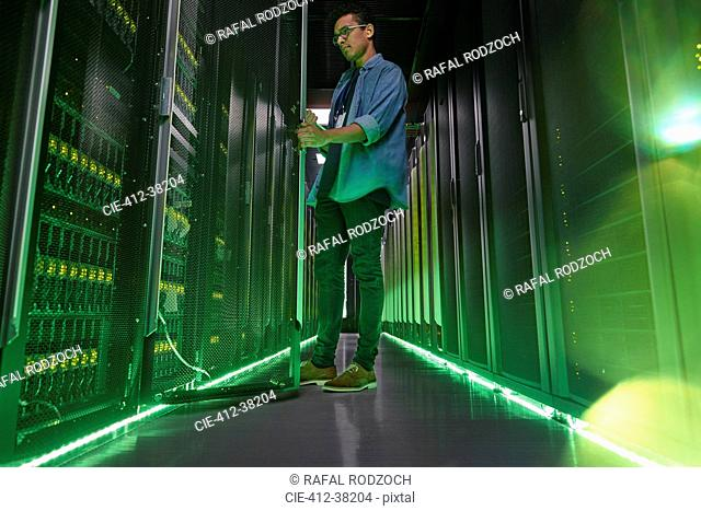 Male IT technician working in dark server room with glowing green panels