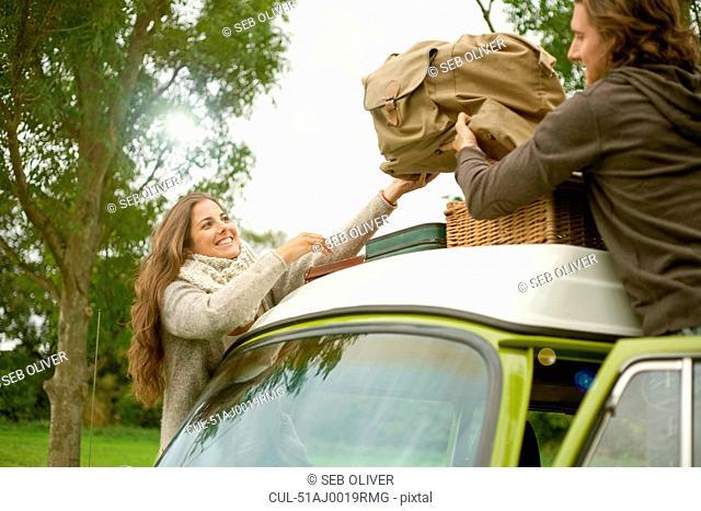 Couple loading luggage onto van