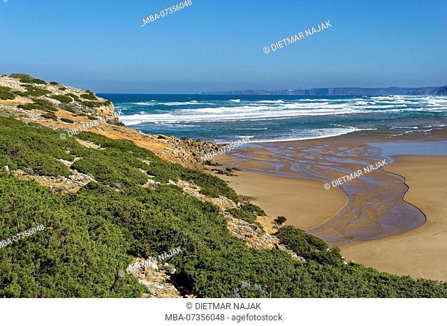 Praia da Bordeira with the mouth of the Ribeira da Carrapateira in the Atlantic Ocean near the small fishing village Carrapateira on the wild rocky coast on the...
