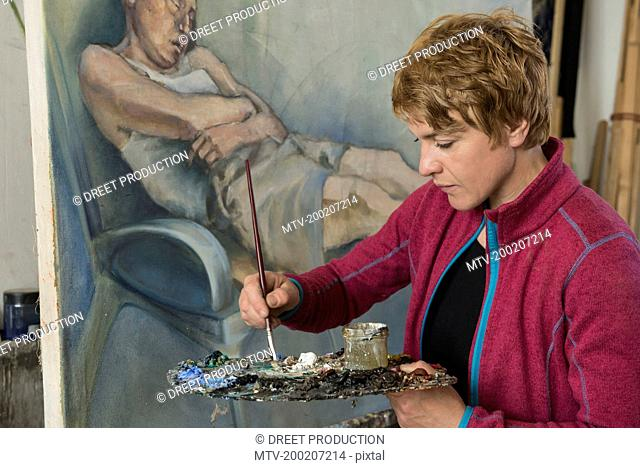 Woman mixing colors while painting, Bavaria, Germany