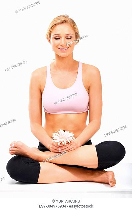 A young beauty holding a flower while meditating - Isolated