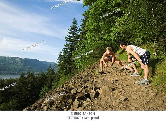Runners stretching on rocky trail