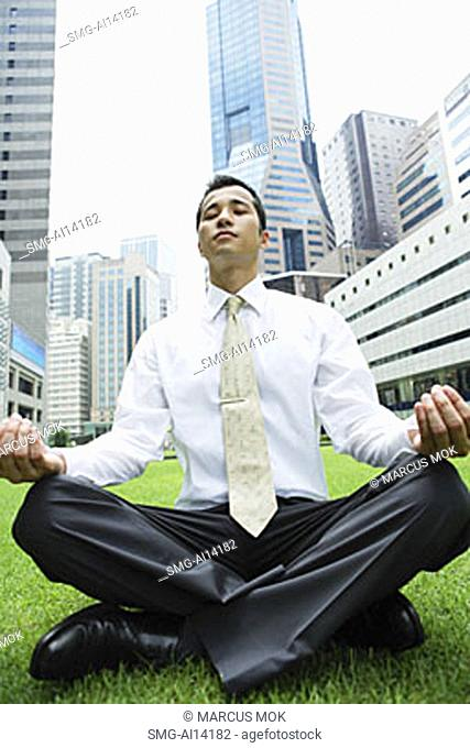 Businessman sitting on grass, legs crossed, buildings in the background