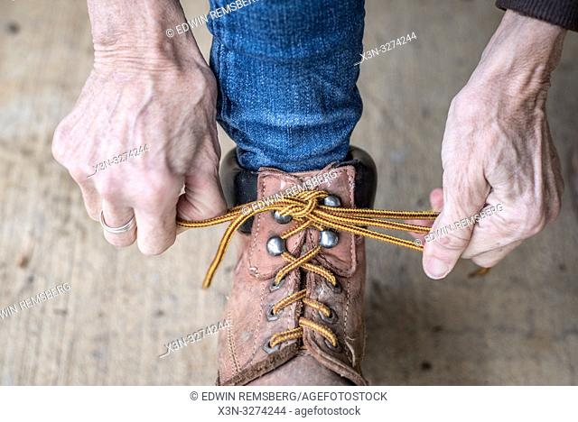 Woman's hands pulls her laces tight on her work boots, Fallston, Maryland