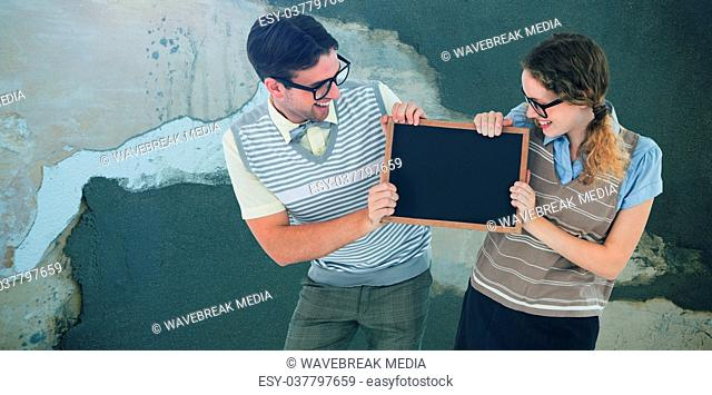 Composite image of geeky hipster couple holding little blackboard