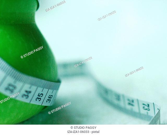 Close-up of a tape measure wrapped around a gourd