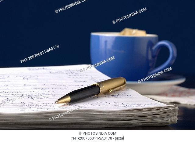 Close-up of a pen on a notepad with a tea cup