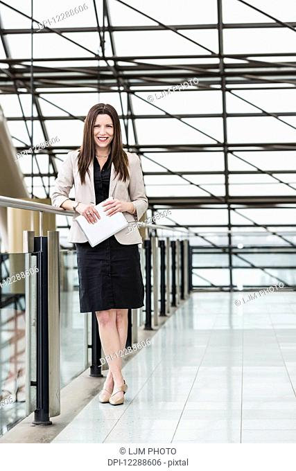 Mature business woman posing in an atrium of an office building and holding a tablet; Edmonton, Alberta, Canada