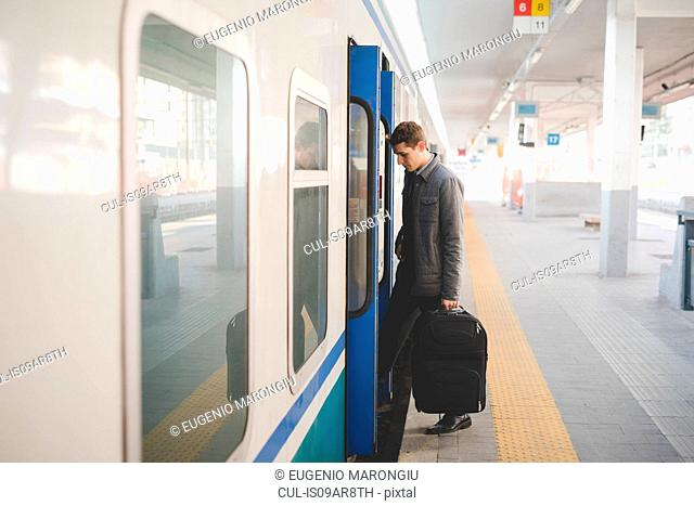 Young businessman commuter boarding train with suitcase