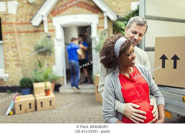 Multi-ethnic pregnant couple moving into new house