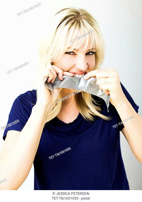 Studio portrait of blonde woman ripping tape