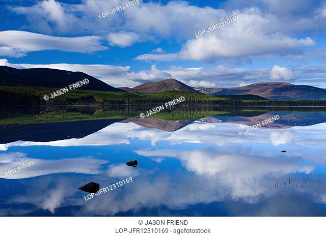 Scotland, Highland, Loch Morlich. Clouds, forest and mountains reflected upon the still waters of Loch Morlich in the Cairngorms National Park