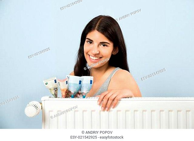 Young Happy Woman With Banknote Inside White Radiator