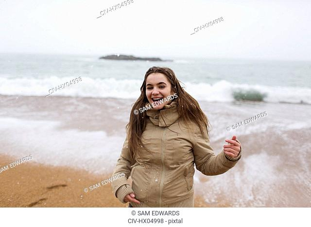 Portrait happy, carefree teenage girl on snowy winter beach