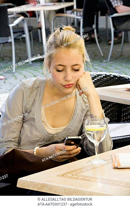 Young woman with mobile waiting in a cafe