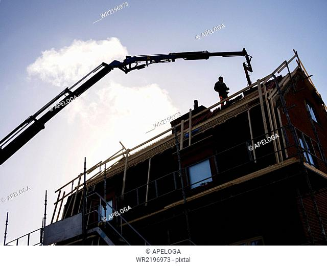 Silhouette of man and crane at construction site