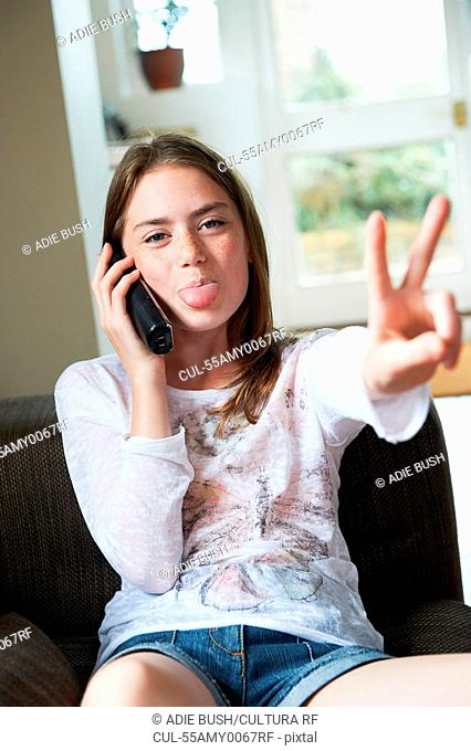 Teenage girl on phone making peace sign with tongue out
