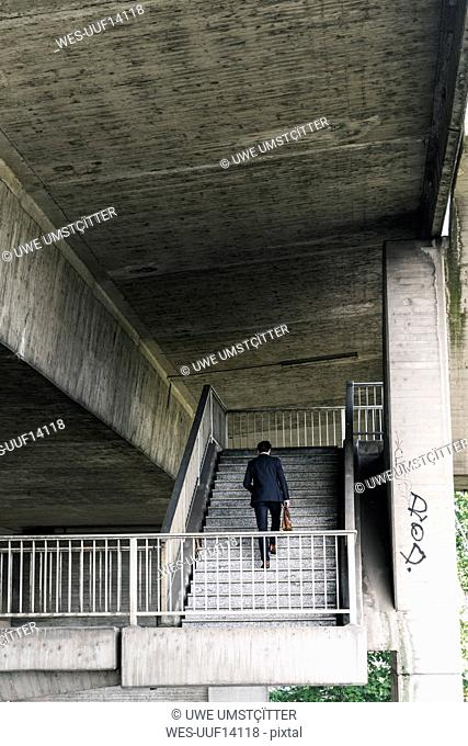 Businessman at underpass walking upstairs