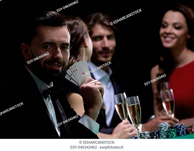 Elegant young smiling people are drinking wine at the poker table