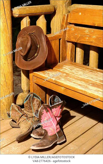 Under a late night sky, worn boots get a well deserved rest in front of a log cabin in Placerville, California. USA