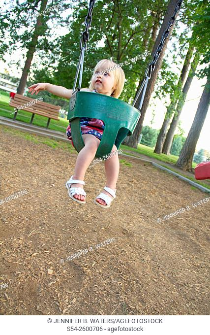 A young female toddler swinging in a child swing at a park in Spokane, Washington, USA