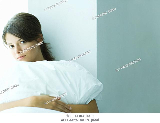 Young woman holding pillow