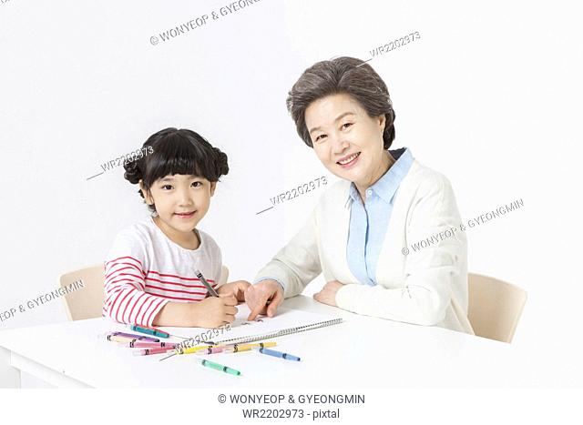 Young girl drawing on sketch pad with color pencils and her grandmother seated right next to her both staring forward with a smile