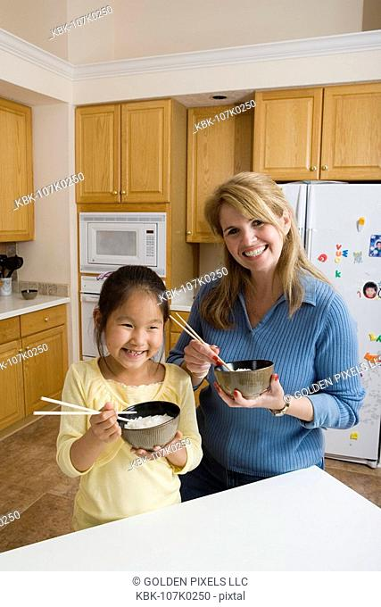 Portrait of mother and daughter in kitchen holding bowls of rice and chopsticks