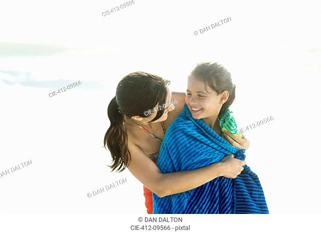Mother wrapping daughter in towel on beach