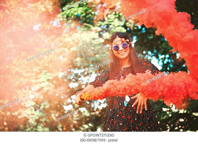 Young boho woman dancing with red smoke flare at festival