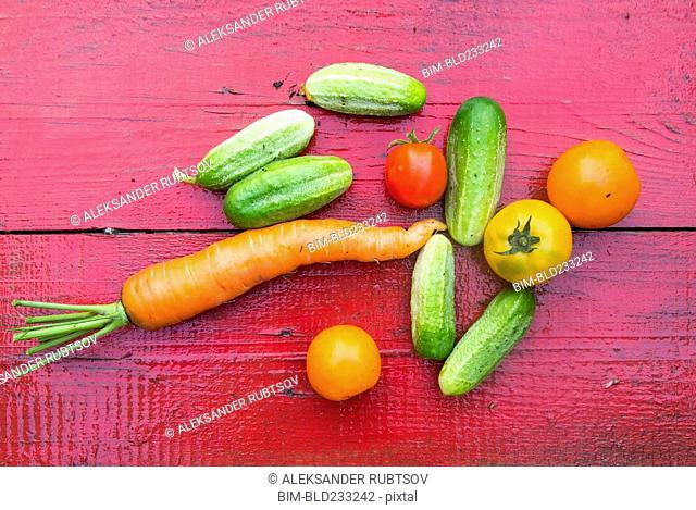 Close up of fresh vegetables on red wooden table