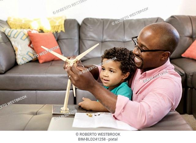 Father and son building model windmill in livingroom