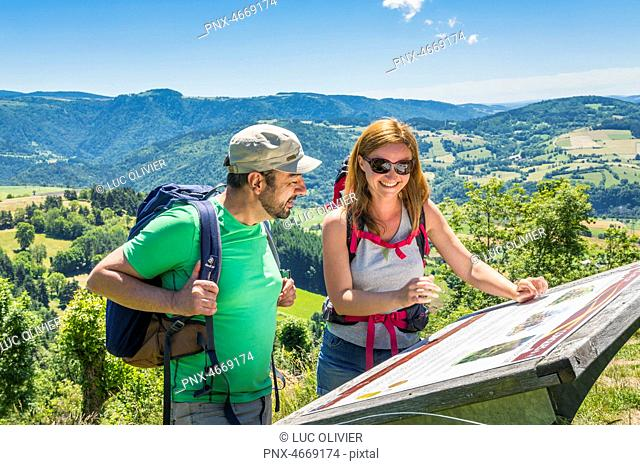 Auvergne - Haute- Loire - The way of Saint James - A couple of hikers reading an information board at the Rochegude chapel, close to Saint-Privat-d'Allier