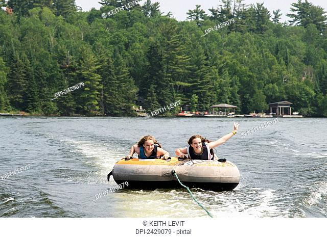 Two teenage girls riding an inner tube being pulled behind a boat in a lake; Ontario, Canada