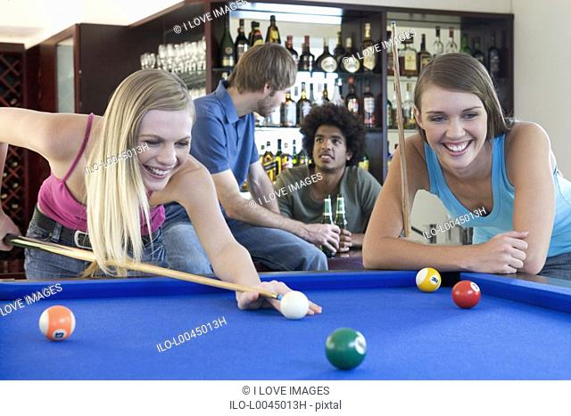 A group of teenage friends playing pool in a bar