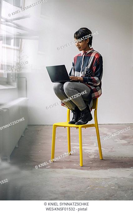 Young woman sitting on chair using laptop