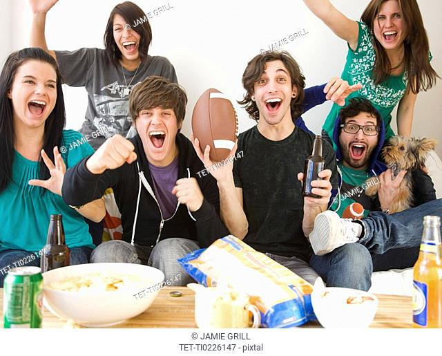 Group of friends cheering on sofa