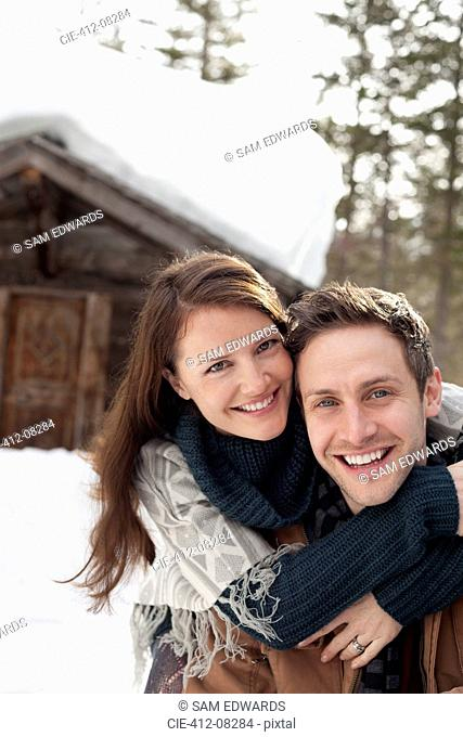 Portrait of happy couple hugging in snow outside cabin