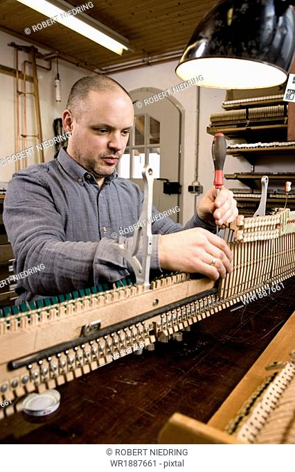 Instrument maker adjusting musical mechanism of a piano, Regensburg, Bavaria, Germany