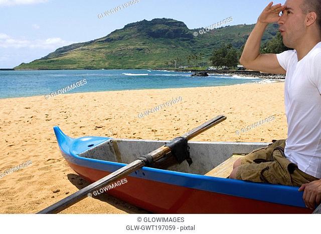 Side profile of a mid adult man sitting in a boat and shielding his eyes on the beach, Nawiliwili Beach Park, Kauai, Hawaii Islands, USA
