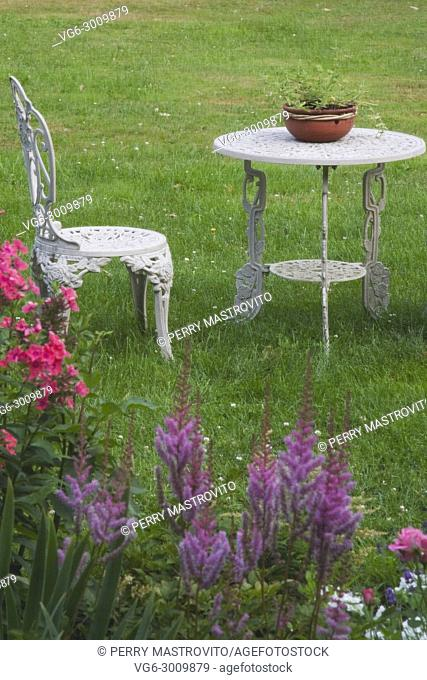 White painted cast iron garden chair and table on the front lawn of a residential home in summer, Quebec, Canada